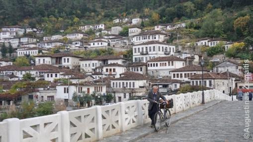 Žmogus eina per seną tiltą Albanijoje