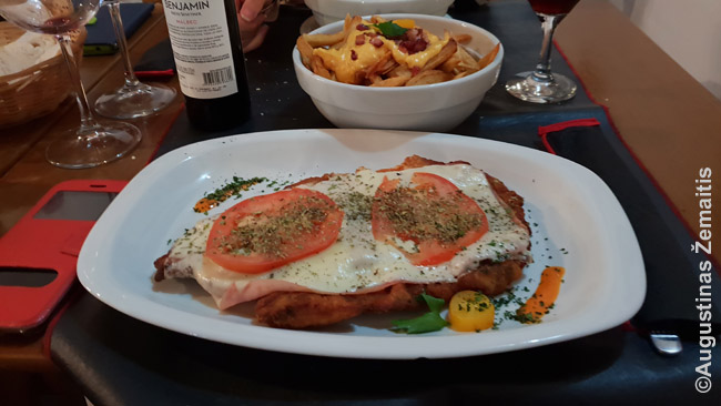 Milanesa su sūriu ir pomidorais vadinama Napolitana. Aukščiau - bulvės, kurios užsakomos kaip atskiras patiekalas, nes šiame restorane (kaip ir daugybėje) prie milanesa joks garnyras nepriklauso