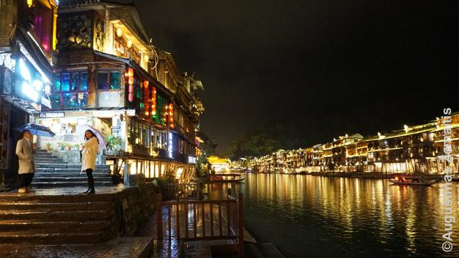 Fenghuangas naktį. Kairėje kvietėjas kviečia į naktinį barą-klubą, iš kurio skamba šokių muzika