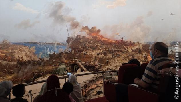 Spalio karo panoramoje. Patirtis susideda iš šiuolaikinio 4D kino ir Šiaurės Korėjos(!) propagandinių menininkų sukurtos panoramos - didžiulio 360 laipsnių kampu supančio  paveikslo, realistiškai atvaizduojančio kaip Egipto pajėgos kerta Sueco kanalą, netikėtumu įveikdamas Izraelio pajėgas. Tolimesnė istorija, kaip Izraelis vėl atstūmė Egiptą atgal, neparodyta.