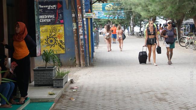 Vietinė su skarele (kairėje) ir kur kas atviriau apsirengę turistai