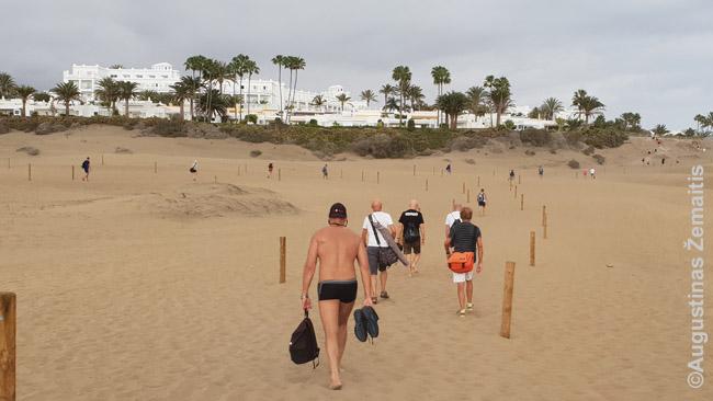 Poilsiautojai grįžta per Maspalomas kopas nuo pakrantės į savo viešbučius (Gran Kanarija)