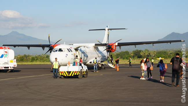 Lėktuvas viename mažų, autobusų stotį primenančių Indonezijos oro uostų. Daug indoneziečių prie lėktuvo fotografuojasi: nors skrydžių daug, kai gyventojų 250 milijonų, dar yra daugybė skrendančių pirmą kartą ar labai retai