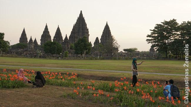 Turistai fotografuojasi per saulėlydį su Prambananu fone