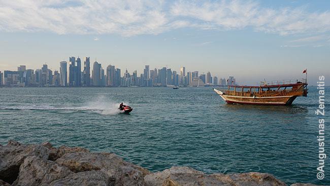 Kataro dangoraižiai, tradicinis laivas ir su vandens motociklu pramogaujantis ekspatas ar turistas