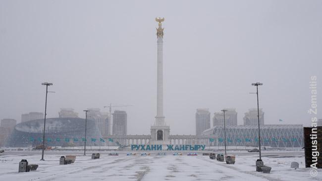 Obeliskas Kazachų tautai ir du geometrinių formų nauji pastatai iš šonų žiemišką Nursultano balandį