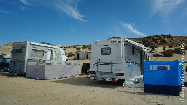 """Stovyklinis keliavimo kemperiu stilius. Čia žmonės kemperiais atvažiavo į vietą Vakarų Sacharoje, tinkamą jėgos aitvarų sportui (kaitavimui). Taigi, jie užsiima šiuo savo hobiu ir praleidžia čia, tikriausiai, savaitę ar ilgiau. Tad gerai prisitaikė stovyklavimui, atsivežė net specialias sieneles, kad suteiktų jų """"kemperio kiemui"""" daugiau privatumo"""