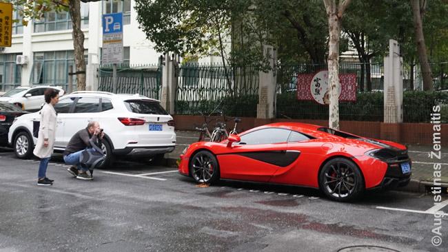 Turistai fortografuoja McLaren automobilį prie Šanchajaus M50 meno rajono