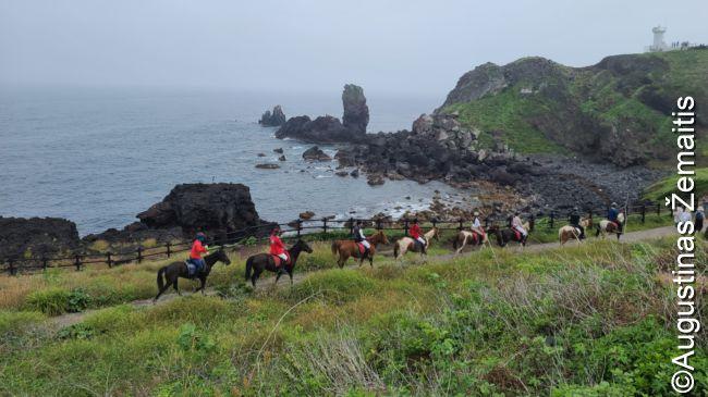 Turistai joja arkliais Čedžu pakrantėje