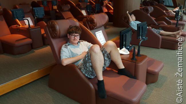 Poilsio foteliai su televizoriais. Šis čimdžilbangas kiek suvakarietintas, nes paprastai gulima ant žemės