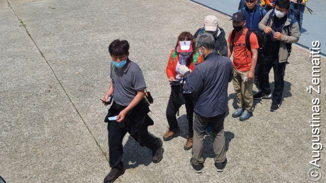 Lipančius į keltą į Bidžindo salą keleivius tikrina termometru