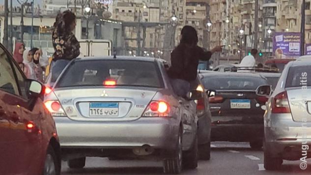 Moterys važiuoja Aleksandrijos pakrante išlindusios pro langus