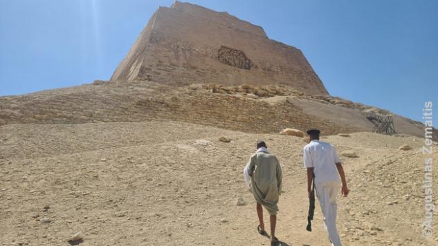 Lipam link piramidės įėjimo su prižiūrėtoju ir jo ginkluota palyda. Kariai iš džipo seka akimis nuo papėdės