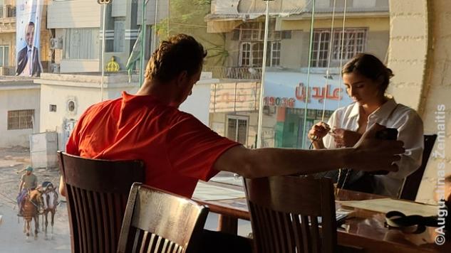 Tipinė pandemijos keliautojų pora iš Amerikos, Gizos restorane sėdėjusi su egiptiečiu gidu
