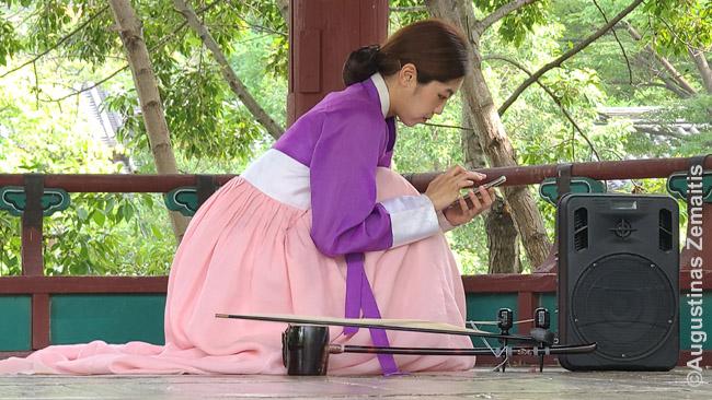 Korėjos liaudies kaimo muzikantė išmaniuoju telefonu reguliuoja garso įrangą - kam tas mikserinis pultas?
