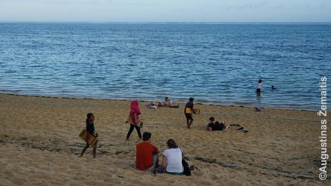 Mergaitės eina per paplūdimį siūlydamos prekes turistams