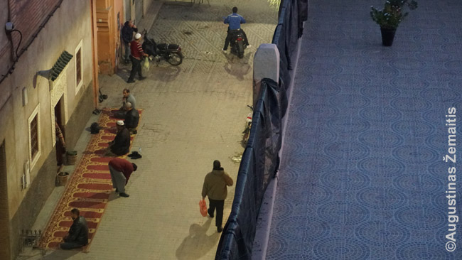 Suskambus muedzinų šauksmui maldai, marakešiečiai meldžiasi tiesiai prieš mečetę