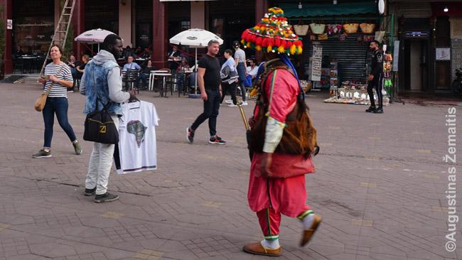Nauji ir tradiciniai Džema El Fna prekijai. Dešinėje - šalto vandens pylėjas (šimtametė profesija), kairėje - juodaodis imigrantas, stumdantis marškinėlius vakariečiams turistams