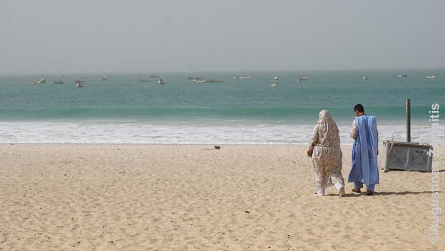 Prisidengę mauritanai savo paplūdimyje. Vandenyne - žvejų laivai