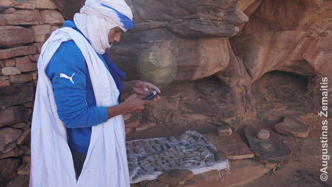 """Petroglifų prižiūrėtojas su išmaniuoju telefonu ir firminiais (ar bent padirbtais) drabužiais po tautiniu daraa. Mauritanija neįstrigusi laike - arba, tiksliau, ne visi jos aspektai įstrigę tame pačiame amžiuje. Tiesa, interneto daugybėje miestelių nėra ir Mauritanija tinka davar Vakaruose madingai skaitmeninei detoksifikacijai, """"internetas kartais naktį būna"""" - sakydavo vietiniai apie Uadaną. Tikrai, kažkada gal 2 nakties atėjo laiškai, bet ir tiek."""