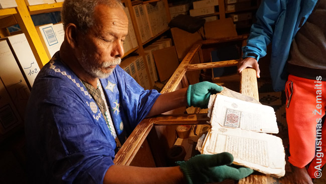 Bibliotekos prižiūrėtojas rodo senus rankraščius