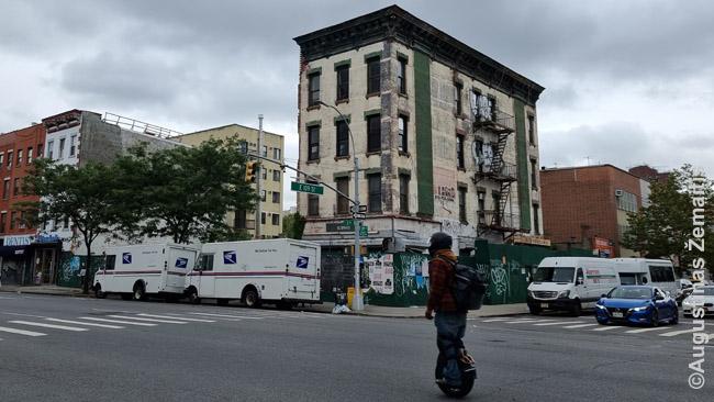 Rytinis Harlemas šiandien. Niujorkietis pro vis dar apleistą namą važiuoja hipsterišku riedžiu.