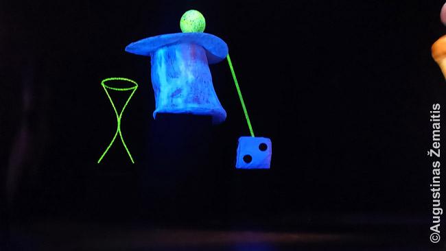 Juodų šviesų teatras. Atrodo, kad juda daiktai, nes jų valdytojai - nematomi.