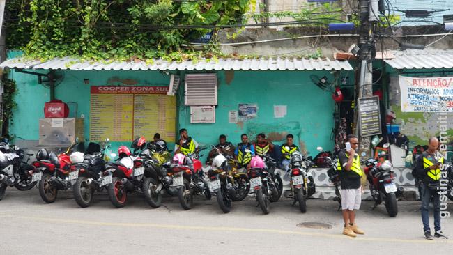 Turistų laukiantys motociklininkai su atšvaitinėmis liemenėmis Vidigalio favelos papėdėje