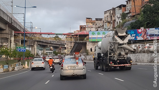 Virš plataus kelio Salvadore iškilusi favela (dešinėje)