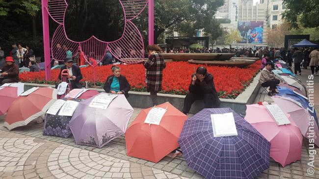 Tėvai su skėčiais Šanchajaus vedybų turguje (miesto Liaudies parke). Karts nuo karto prieina pakalbėti vienas prie kito, apsikeičia kontaktais.