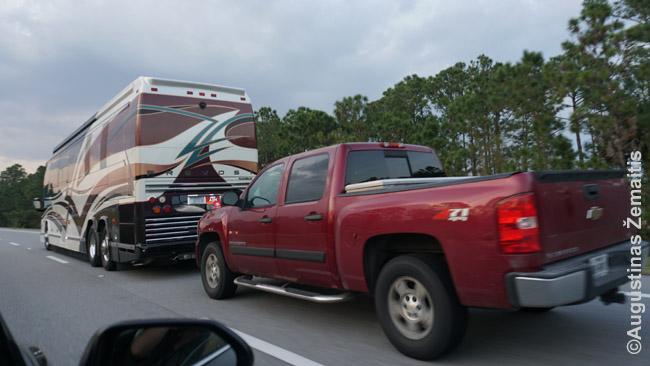 NASCAR gerbėjai atvaiuoja prie trasos milžinišku kemperiu, o iš galo velka pikapą - kad, pasistatę kemperį, galėtų po apylinkes važinėti pikapu