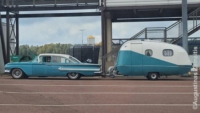 Suomiai su senu automobiliu ir priderinta gyvenamąja priekaba laukia eilės į keltą