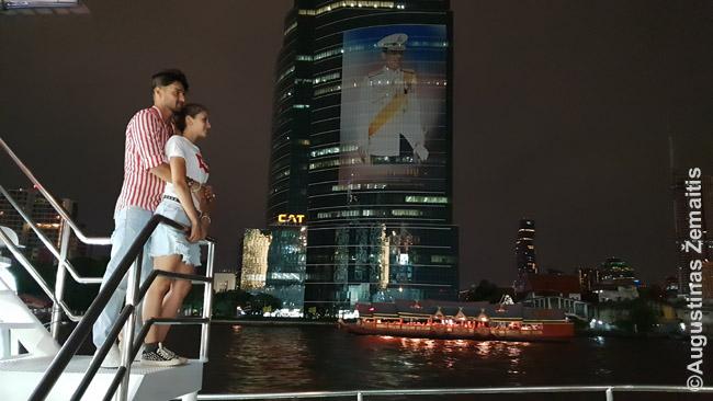 """""""Vakarienės kruizas"""" praplaukia pro dangoraižį su karaliaus nuotrauka Bankoke"""