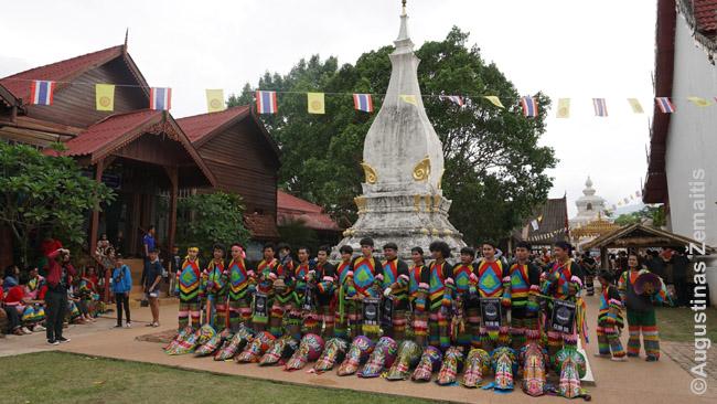 Šventei einant link pabaigos vieno Phi Ta Khon klubų nariai nusiėmę kaukes prie miesto šventyklos pozuoja šventės lankytojams