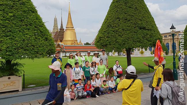 Turistų-ekskursantų grupė sustatyta bendrai nuotraukai prie Tailando karalių rūmų