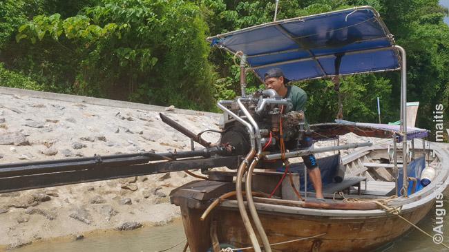 Vairuotojas užvedinėja ilgauodegį laivą. Jo esmė - labai paprasta: ant medinės valties - automobilio variklis. Uodega ilga, kad variklis neperšlaptų - juk jis neskirtas laivui.