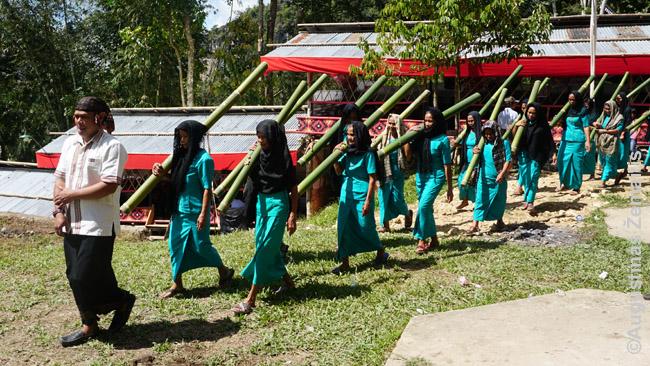 Kaimo moterys specialiais rūbais eina lankyti mirusiosios šeimos