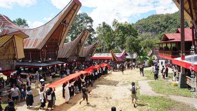 Moterų procesija su raudonuoju audeklu seka paskui lavono palankiną