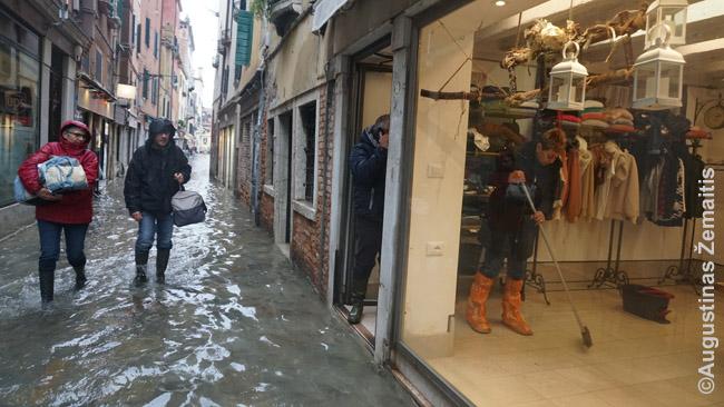 Slūgstant potvyniui praeiviai brenda pro parduotuvę, kurios pardavėjos mėgina iššluoti vandenį lauk