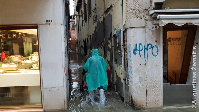 Žmogus specialiais antbačiais brenda gatve, o pompos iš pirmojo aukšto pumpuoja vandenį