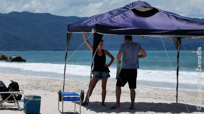 Santa Katarinos paplūdimyje porelė statosi palapinę. Taip paplūdimiuose praleidžiama visa diena